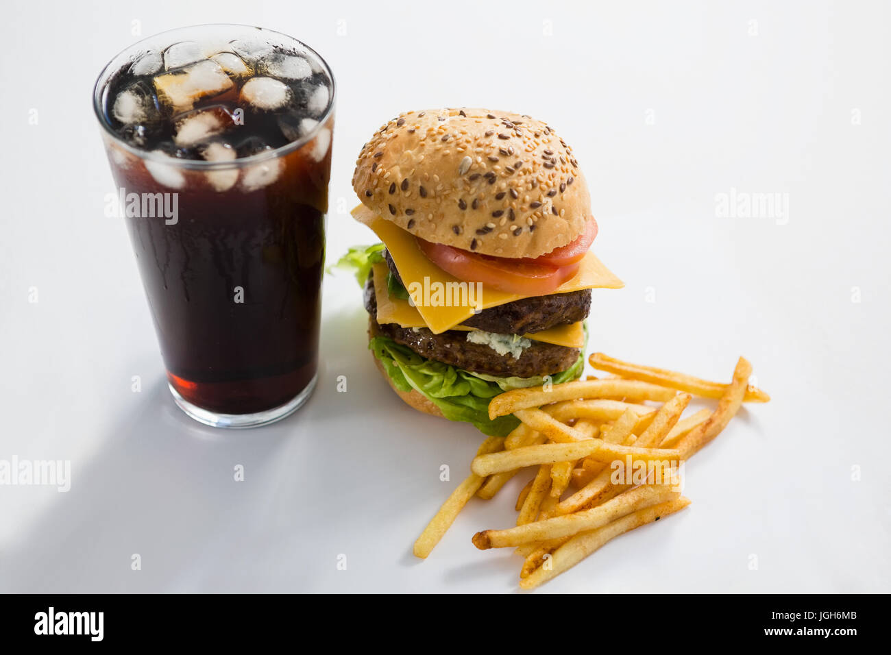 Cheeseburger and drink with French fries on white background - Stock Image