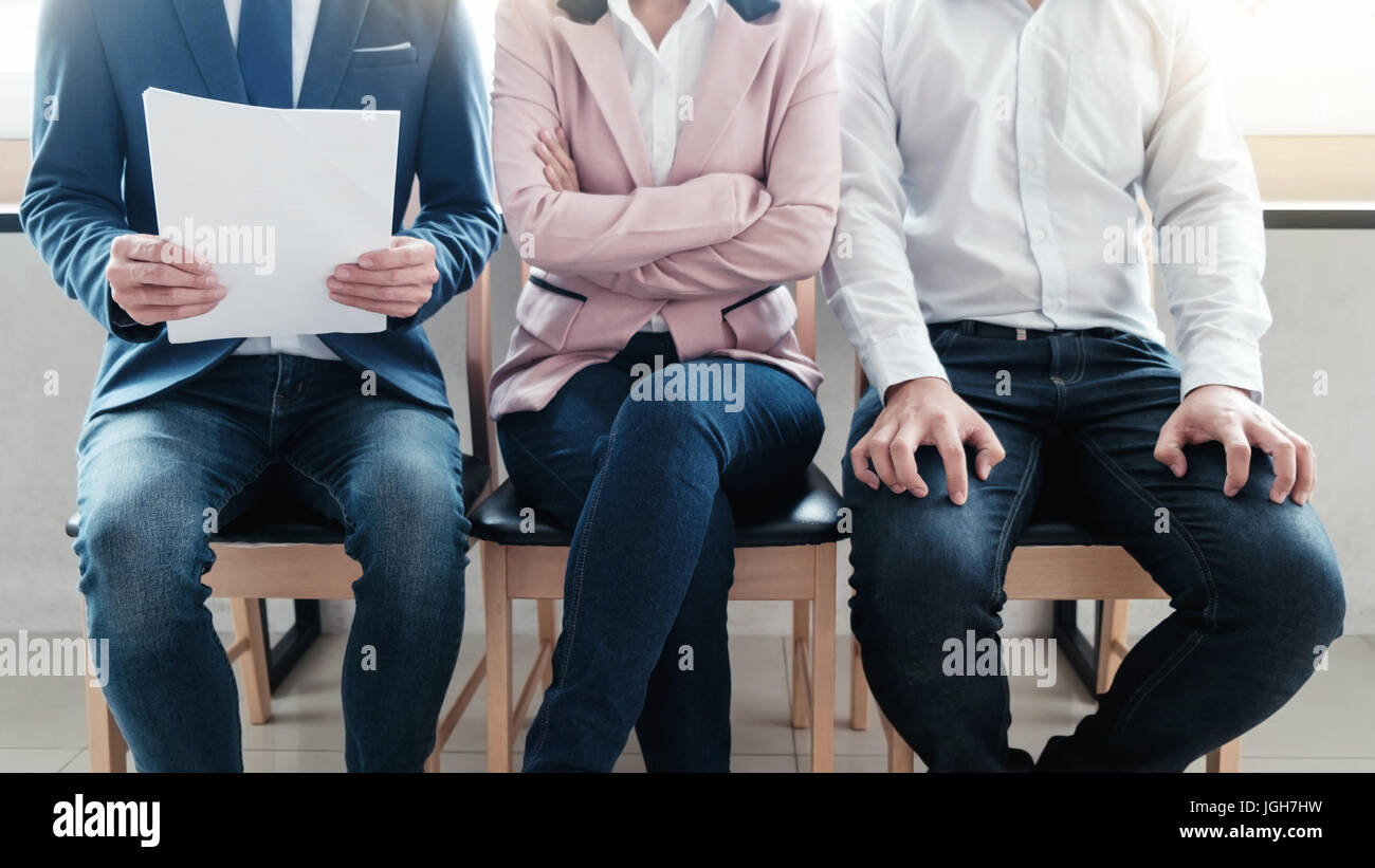 Line of young business people  sitting waiting for their turn for interview - Stock Image