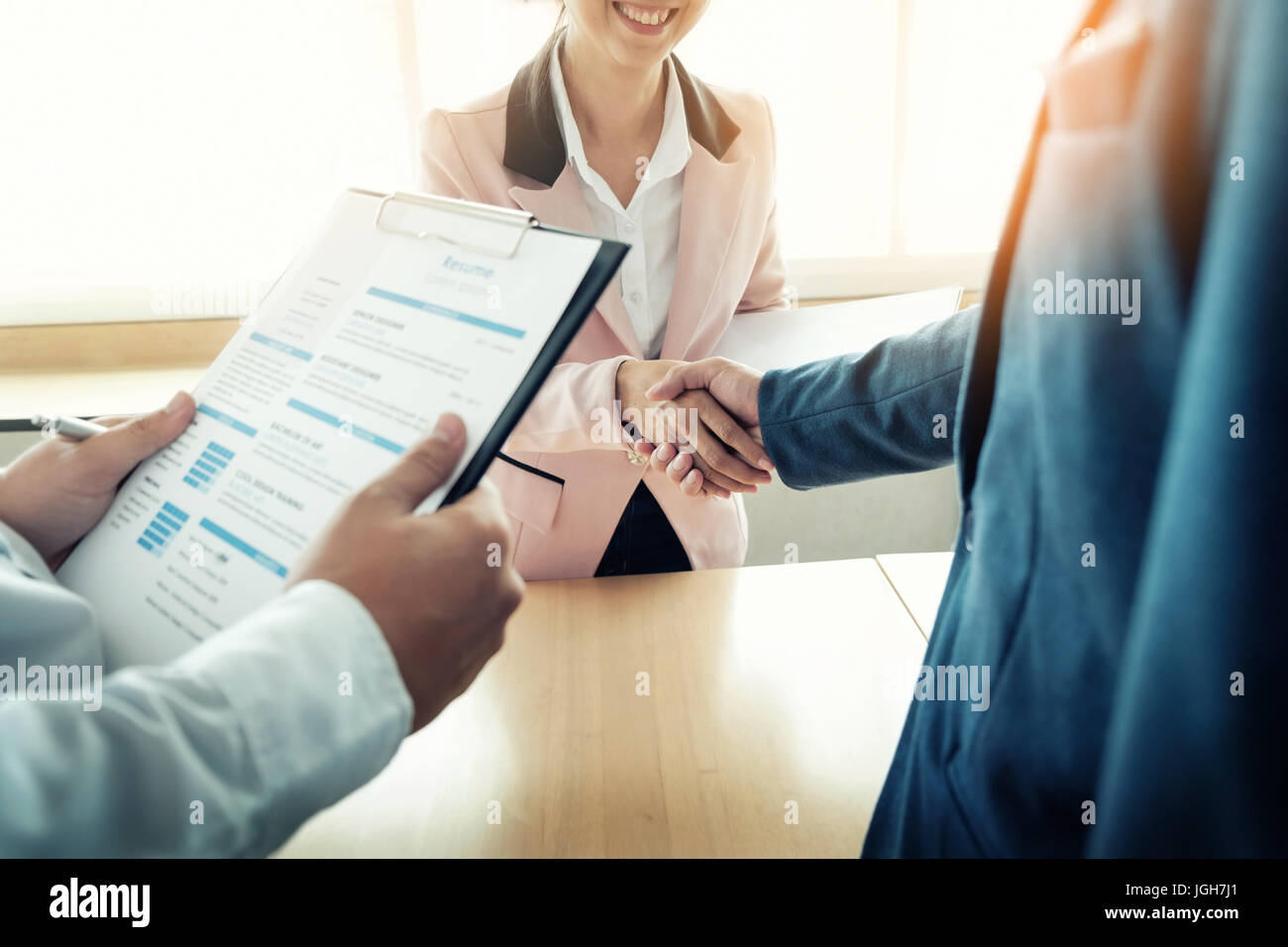 of successful business team shaking hands with eachother in the office, job interview concept. - Stock Image