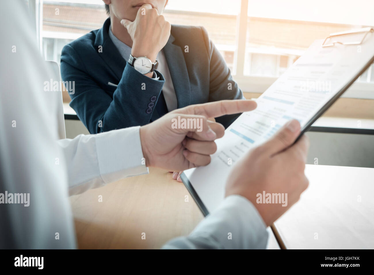 business man interviewer looking skeptical while listening to an asian female interview - Stock Image