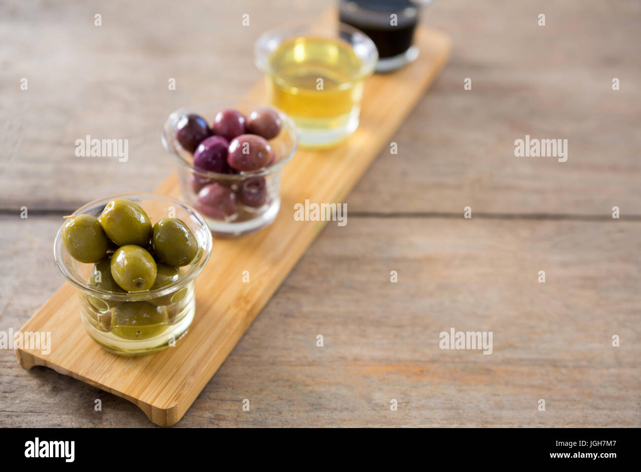 beee6cd22c7f Close-up of marinated olives with olive oil and balsamic vinegar in glass  container on a wooden tray