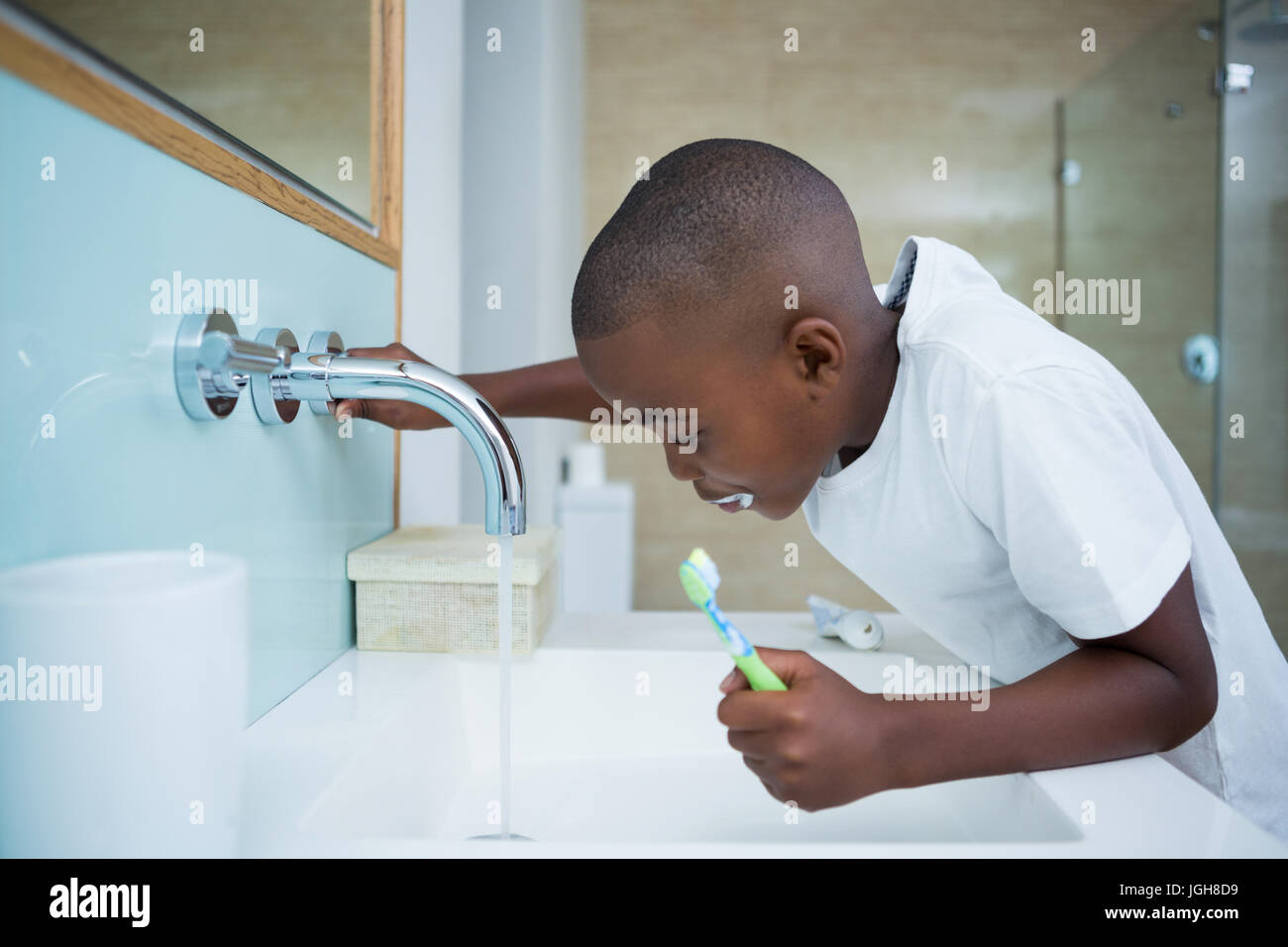 Side View Of Boy Spitting While Holding Brush In Sink At