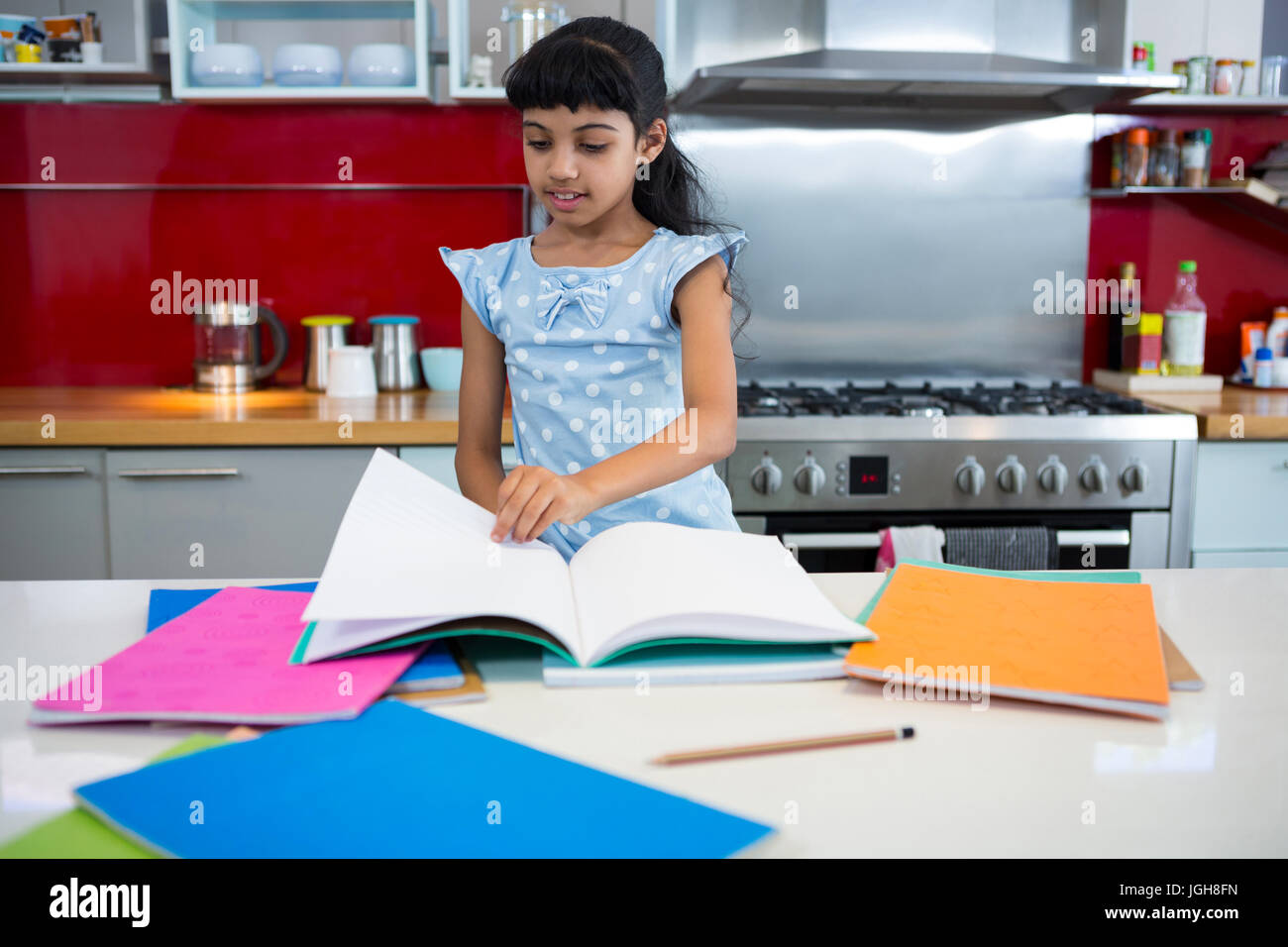 Girl flipping pages of book in kitchen at home - Stock Image