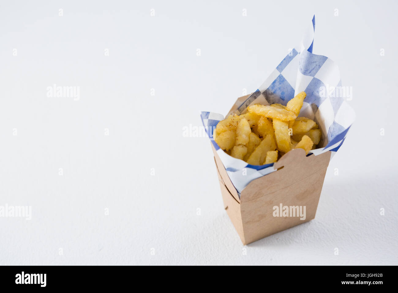 High angel view of French fries in carton box on table - Stock Image