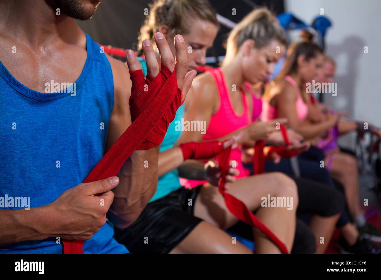 Row of athletes wrapping bandages on hands at fitness studio - Stock Image