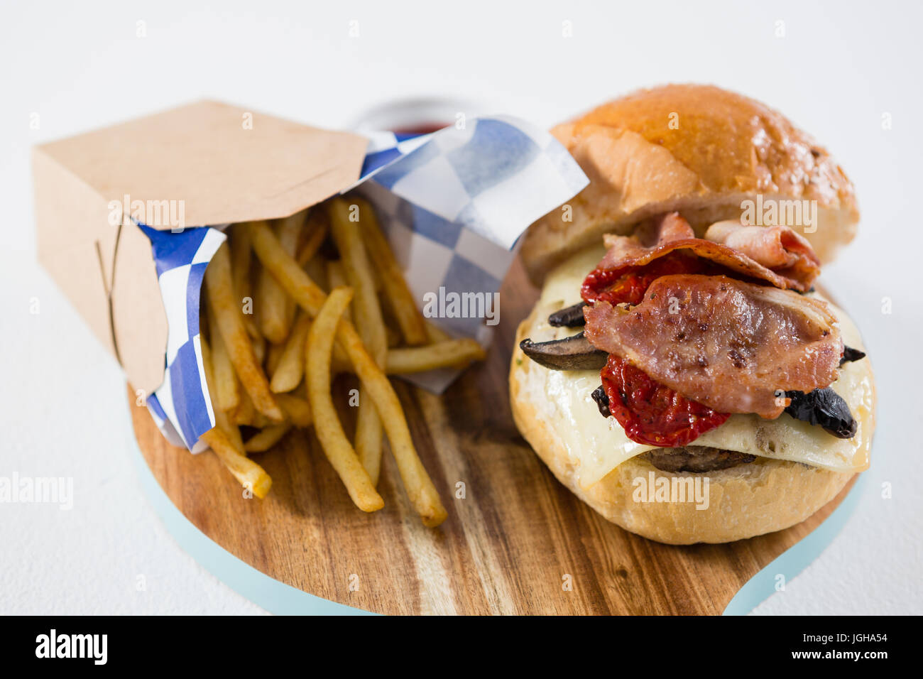 High angel view burger and French fries on cutting board - Stock Image