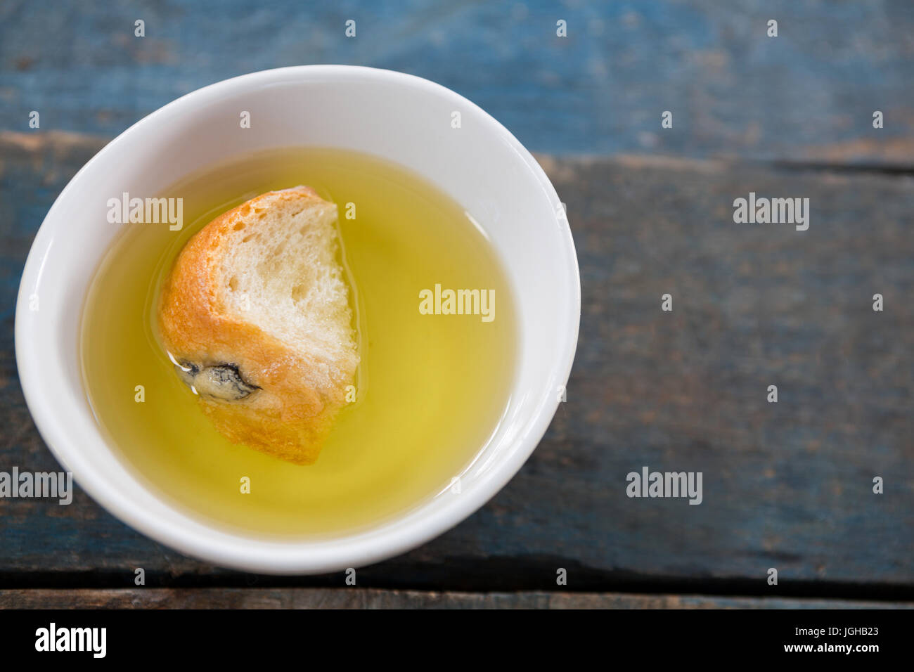 Piece of bread soaked in olive oil in white bowl - Stock Image