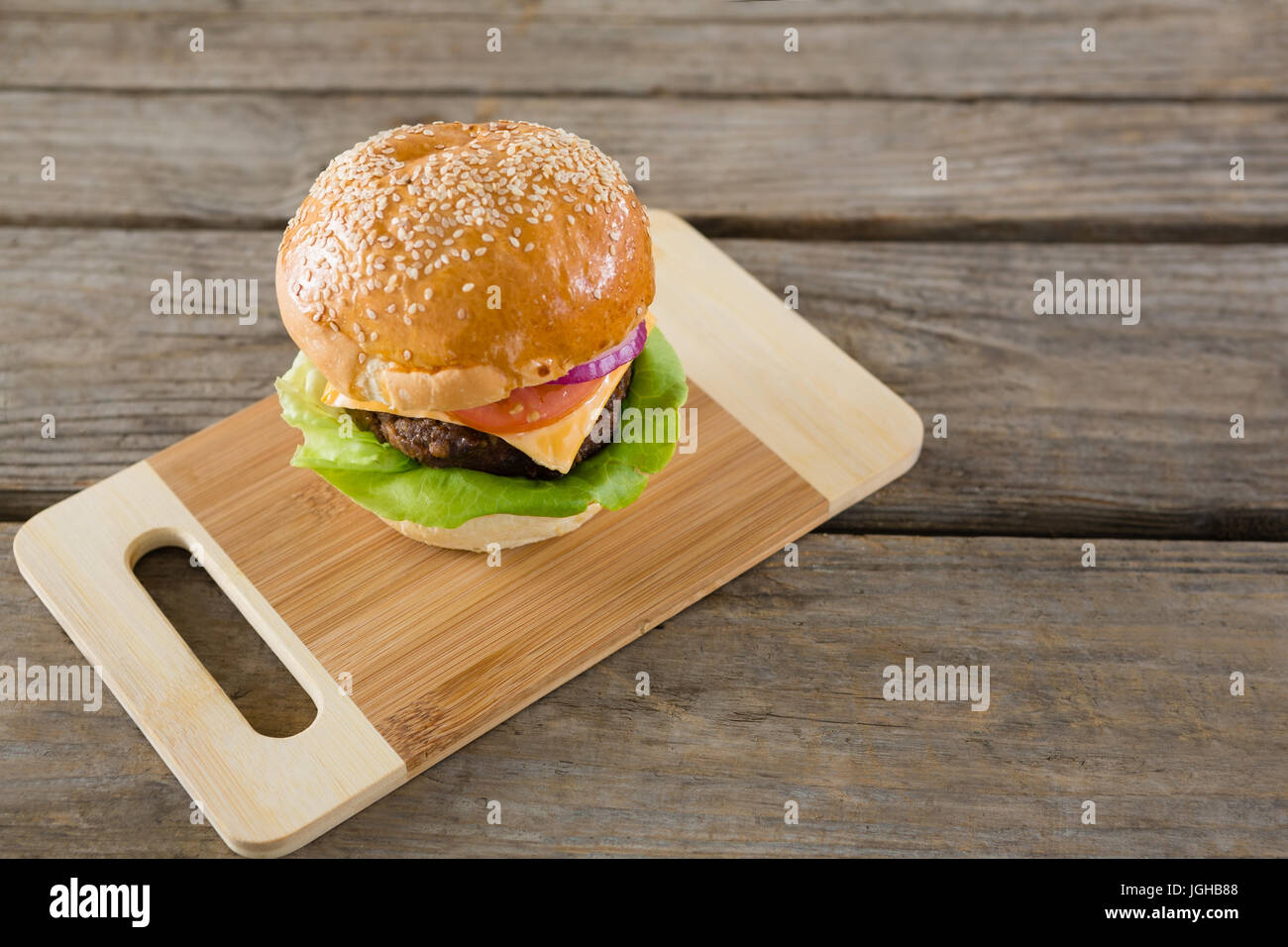High angel view of hamburger with cheese on cutting board at wooden table - Stock Image