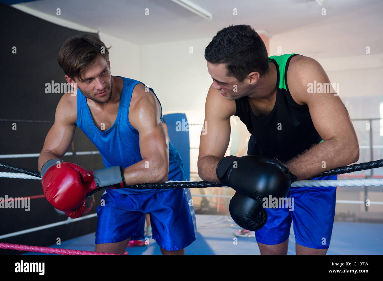 Young male boxers leaning on boxing ring rope Stock Photo