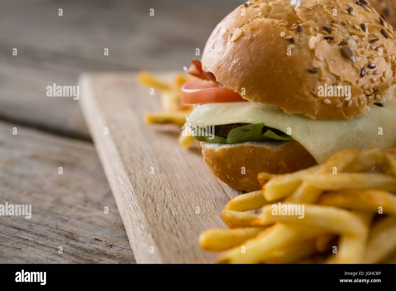 Close up of cheeseburger with french fries served on cutting board Stock Photo