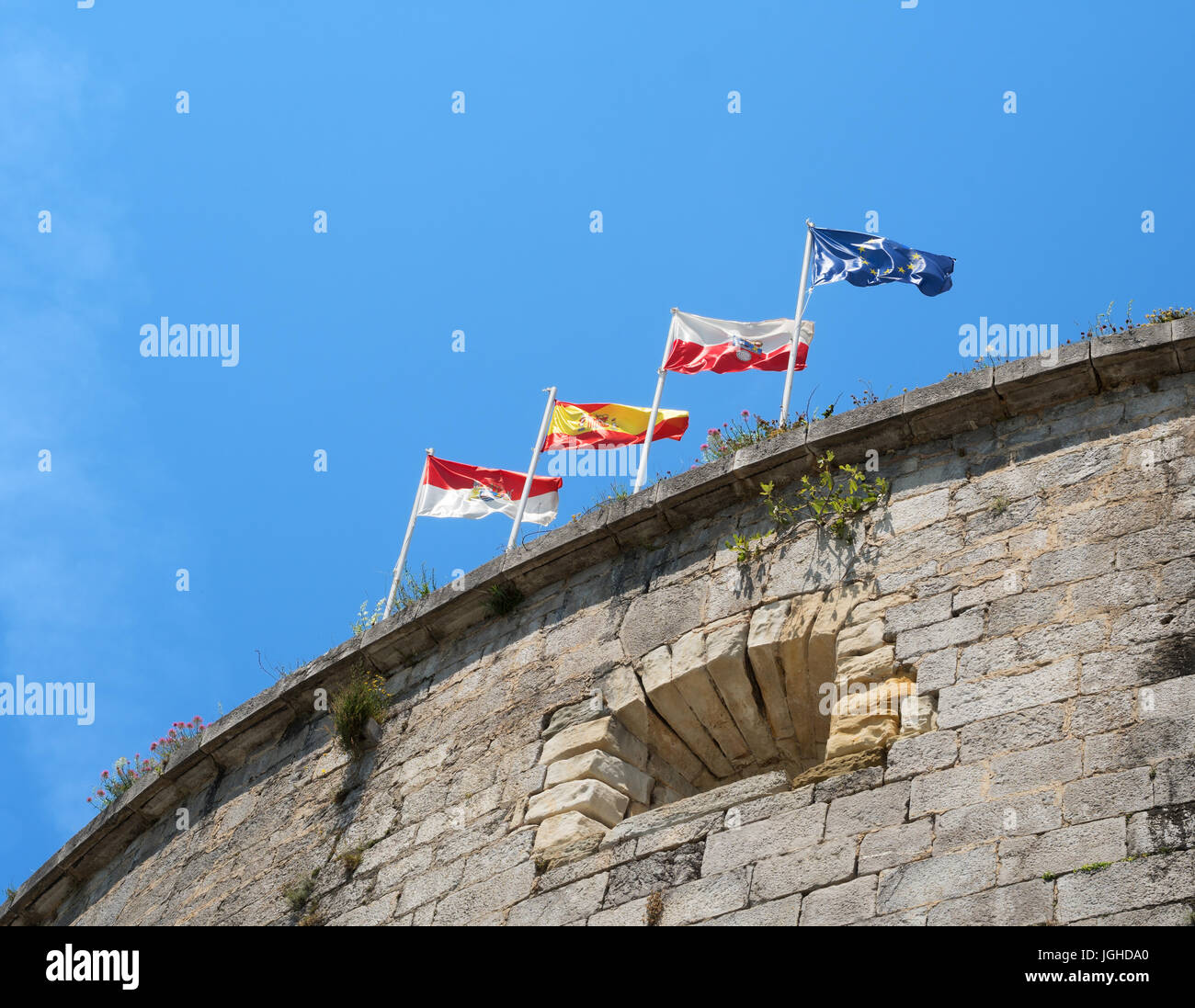 Flags flying over the Fort of San Martin, Santona, Cantabria, Spain - Stock Image