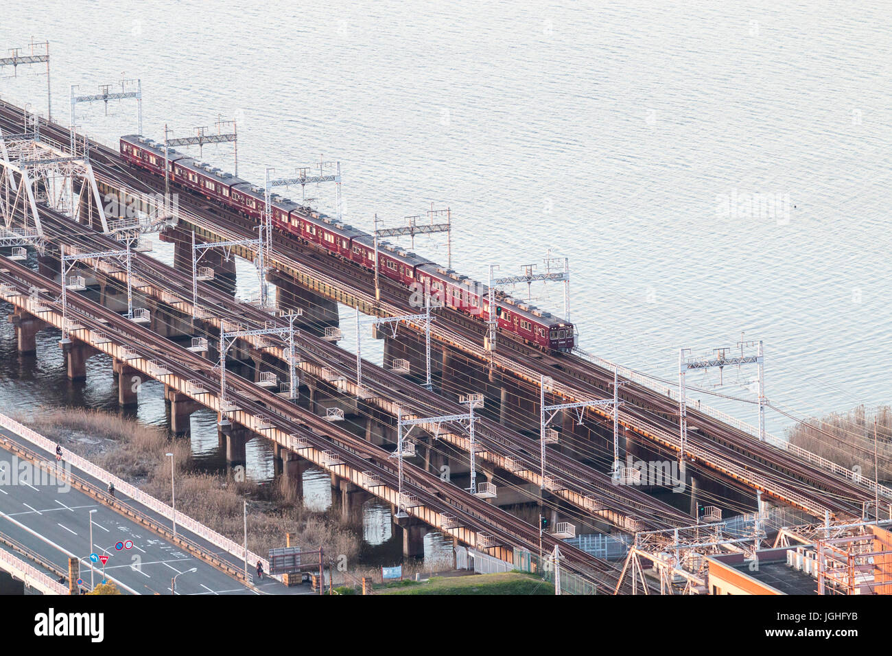 Aerial view of Hankyu railway bridge, three each with two tracks on, over the Yodogawa river with maroon coloured - Stock Image