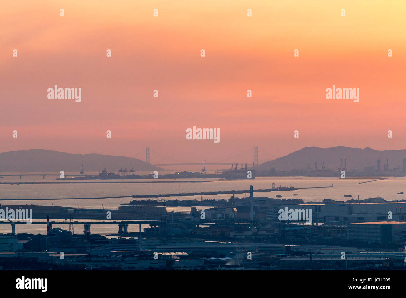 Distant shot. Docks and bridges of Osaka, beyond, the mountains and Akashi Kaikyo suspension bride over the Inland - Stock Image