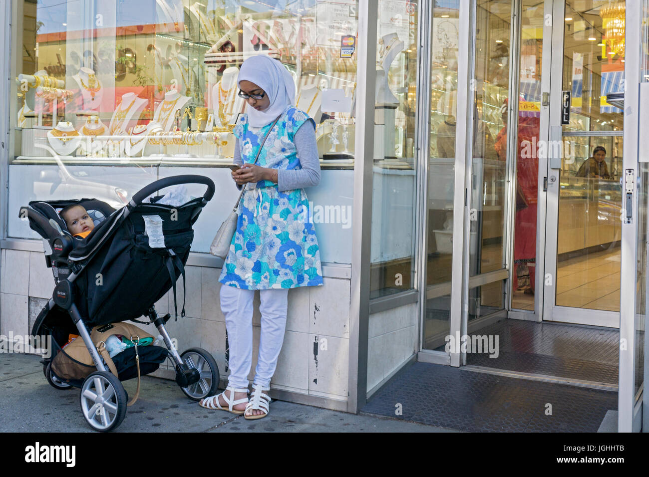 A young Muslim woman looking at her cell phone near a baby carriage in front of a jewelry store on 74th St. In Jackson - Stock Image