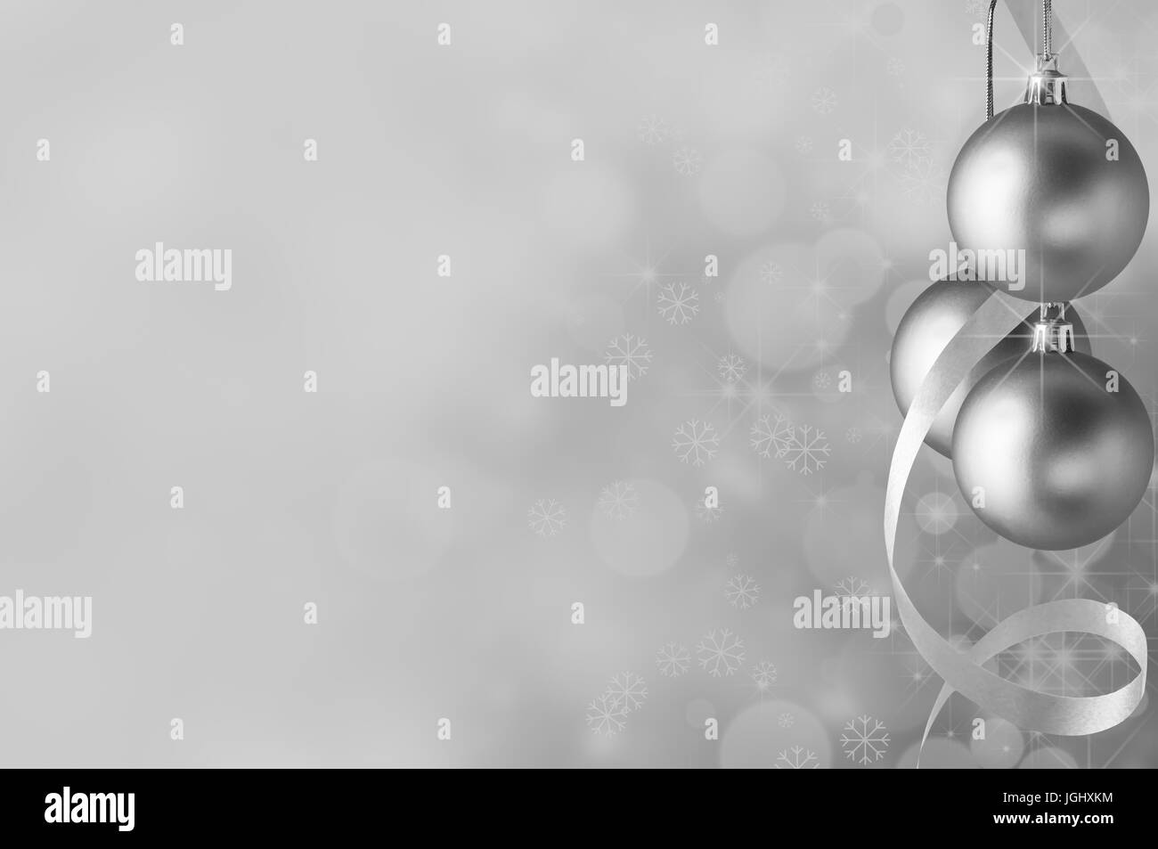 Festive silver Christmas baubles and spiral streamer on the right. Circles of bokeh glow, sparkling stars and snowflakes - Stock Image