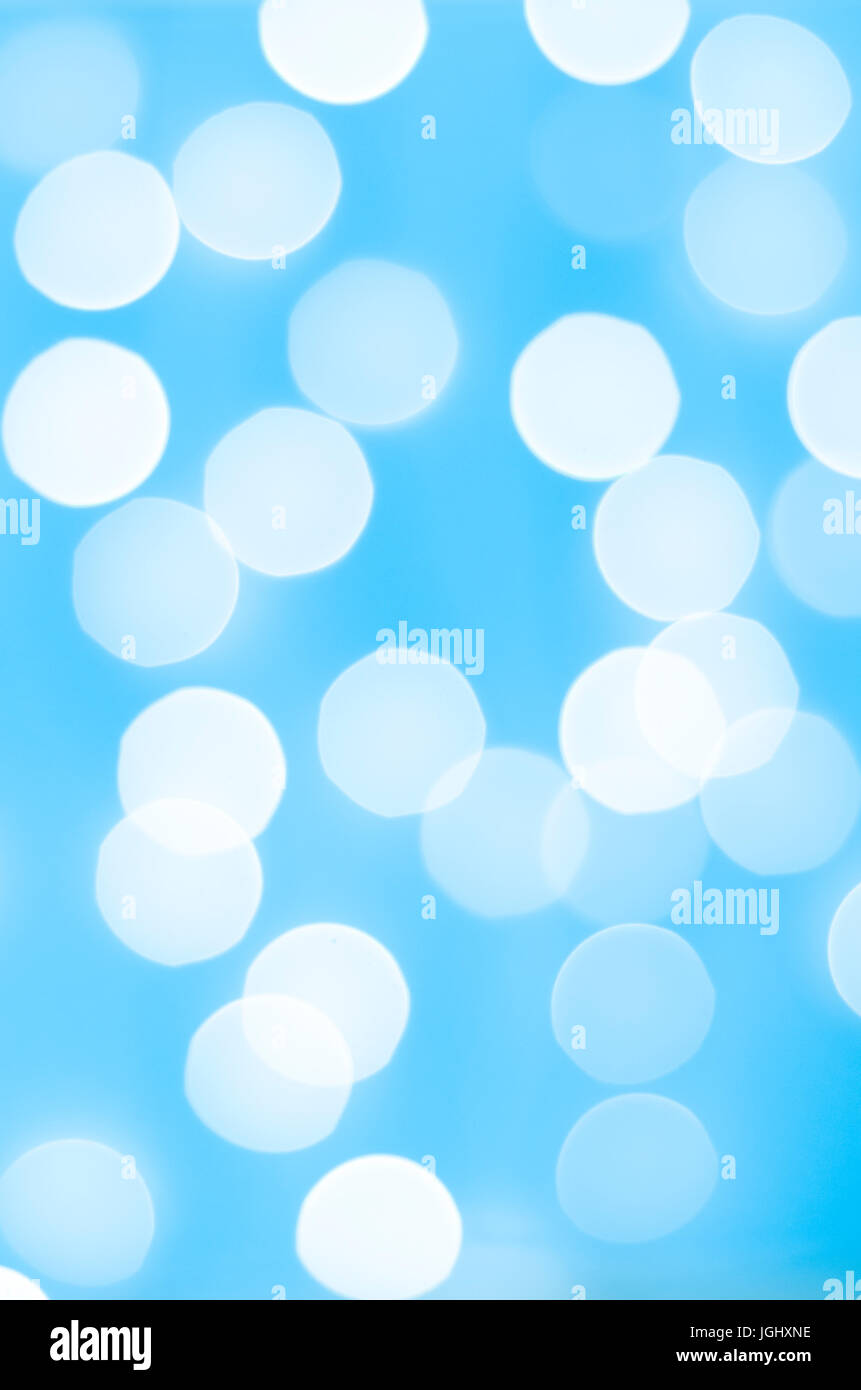 Photographed bokeh lights background in light, bright blue and white. - Stock Image