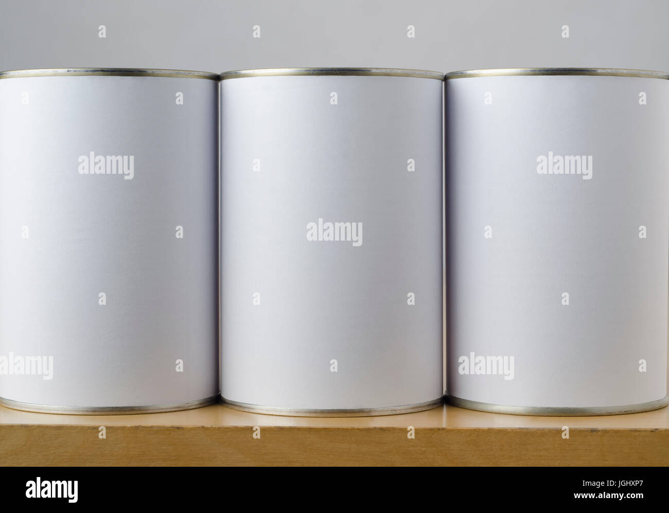 Conceptual image of three tin cans with blank white paper labels on a shelf, copy space on labels allows inclusion - Stock Image
