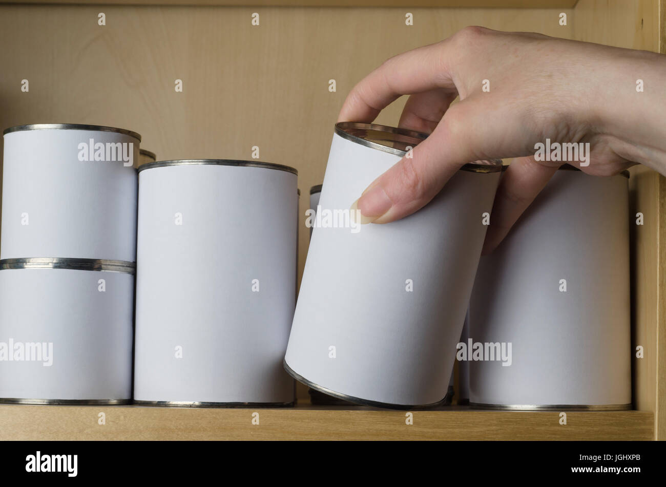 A selection of tin cans in various sizes on a shelf, with female hand reaching in from the right to select one. - Stock Image