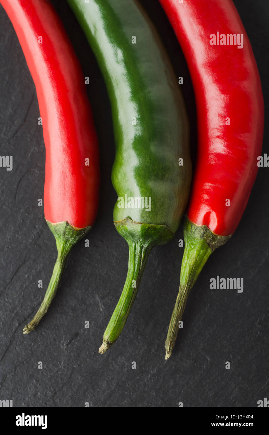 Close up of three chili peppers shot from above on black slate.  Green in the centre, with red peppers either side. - Stock Image