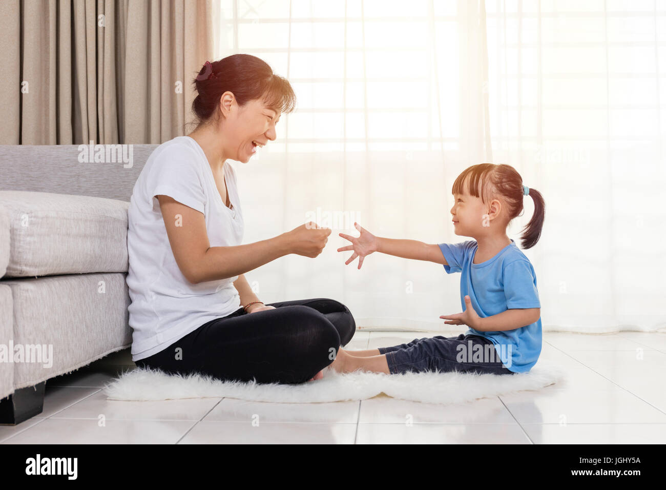 Asian Chinese mother and daughter playing rock-paper-scissors in the living room at home. - Stock Image