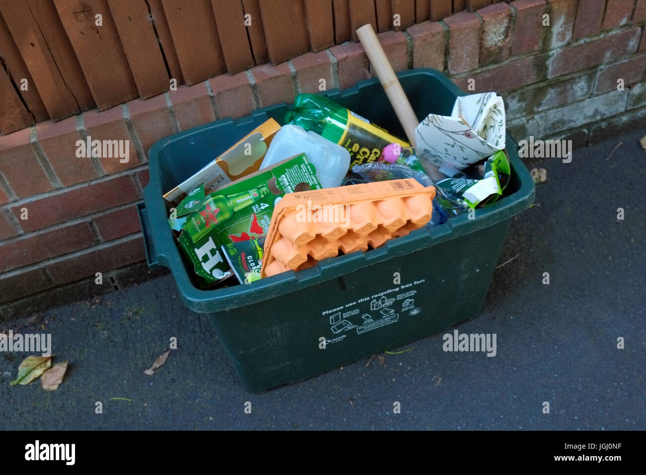 A green recycling bin outside a house in Bristol, UK - Stock Image