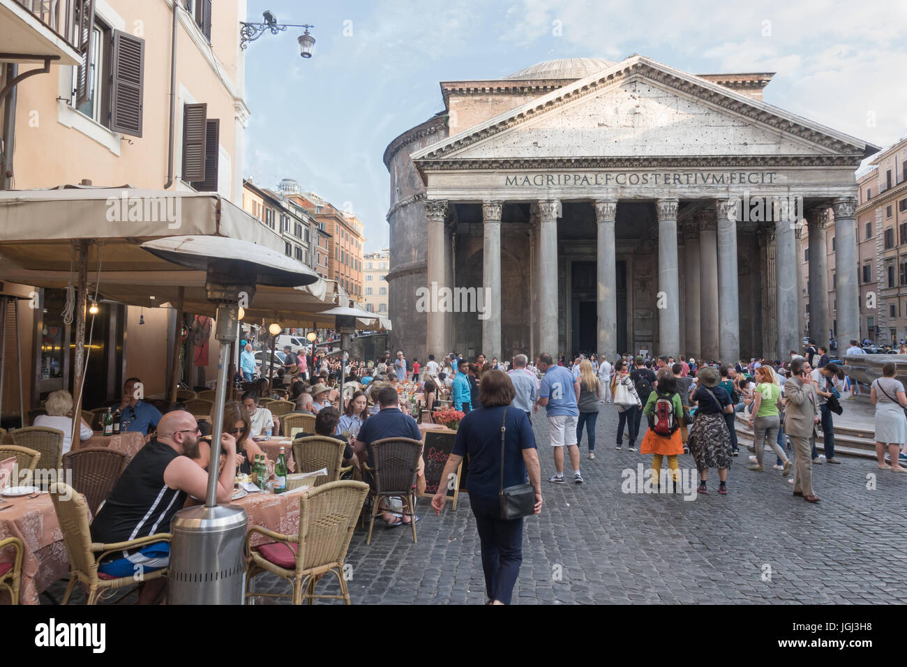 Early evening tourists enjoy cafe and sights in front of ancient Pantheon, Rome, Italy. Sun setting, scenic, no Stock Photo
