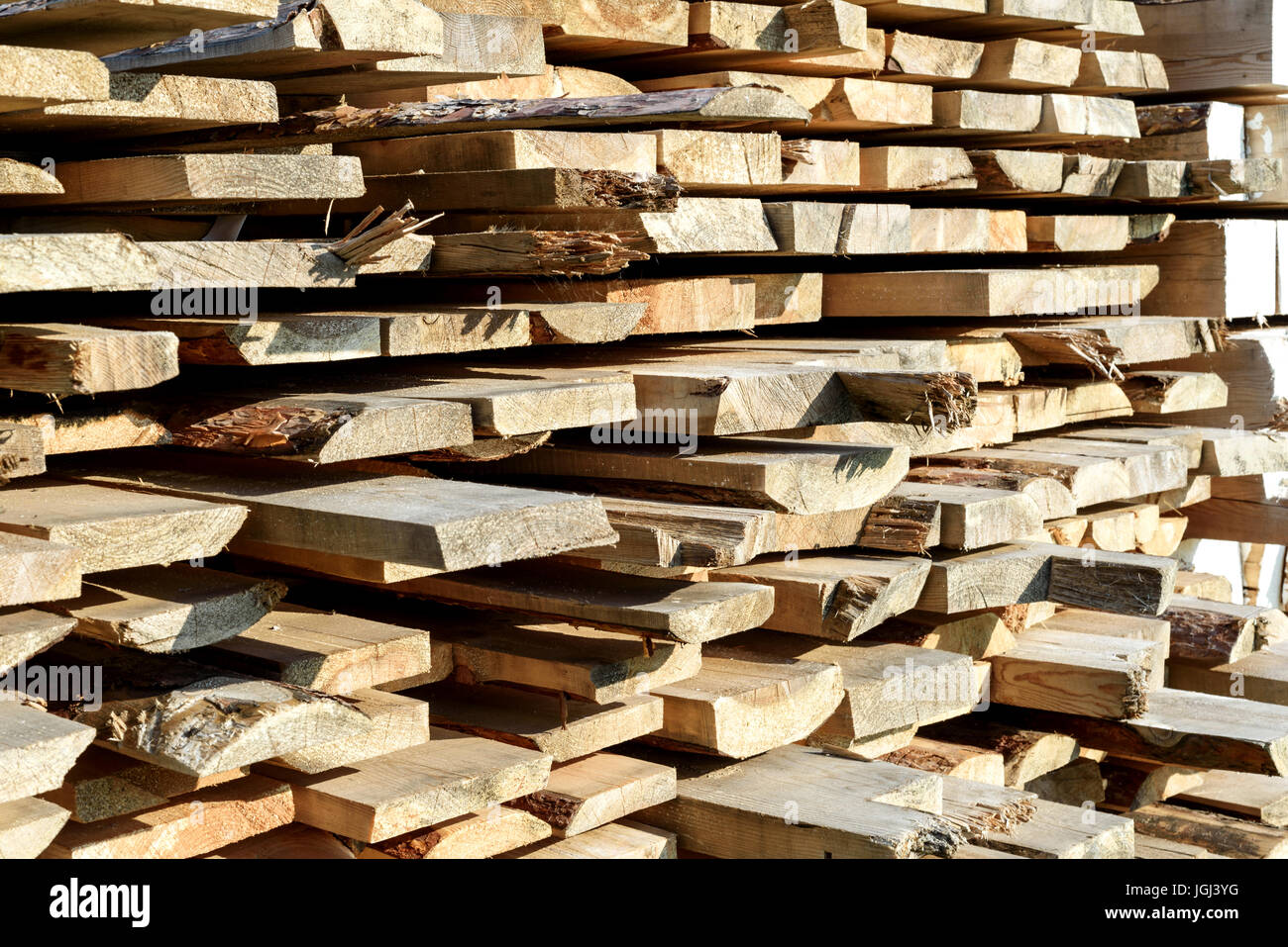 Roughly cut piles of timber planks for home and design construction in sunlight Stock Photo