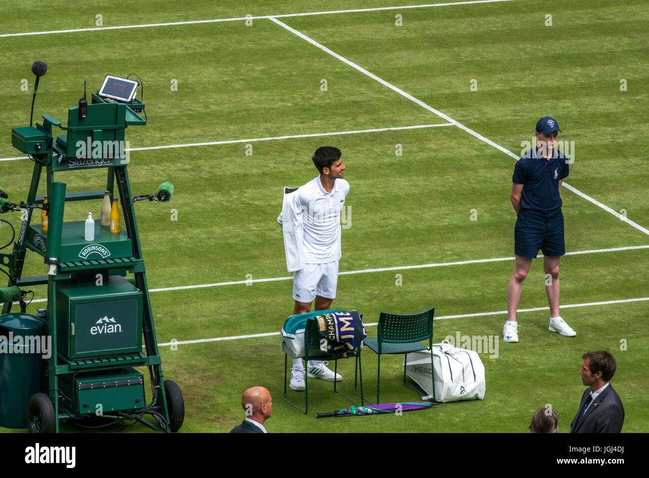 Novak Djokovic takes off jacket on Centre court, grand slam match against Martin Klizan Wimbledon tennis championship - Stock Image