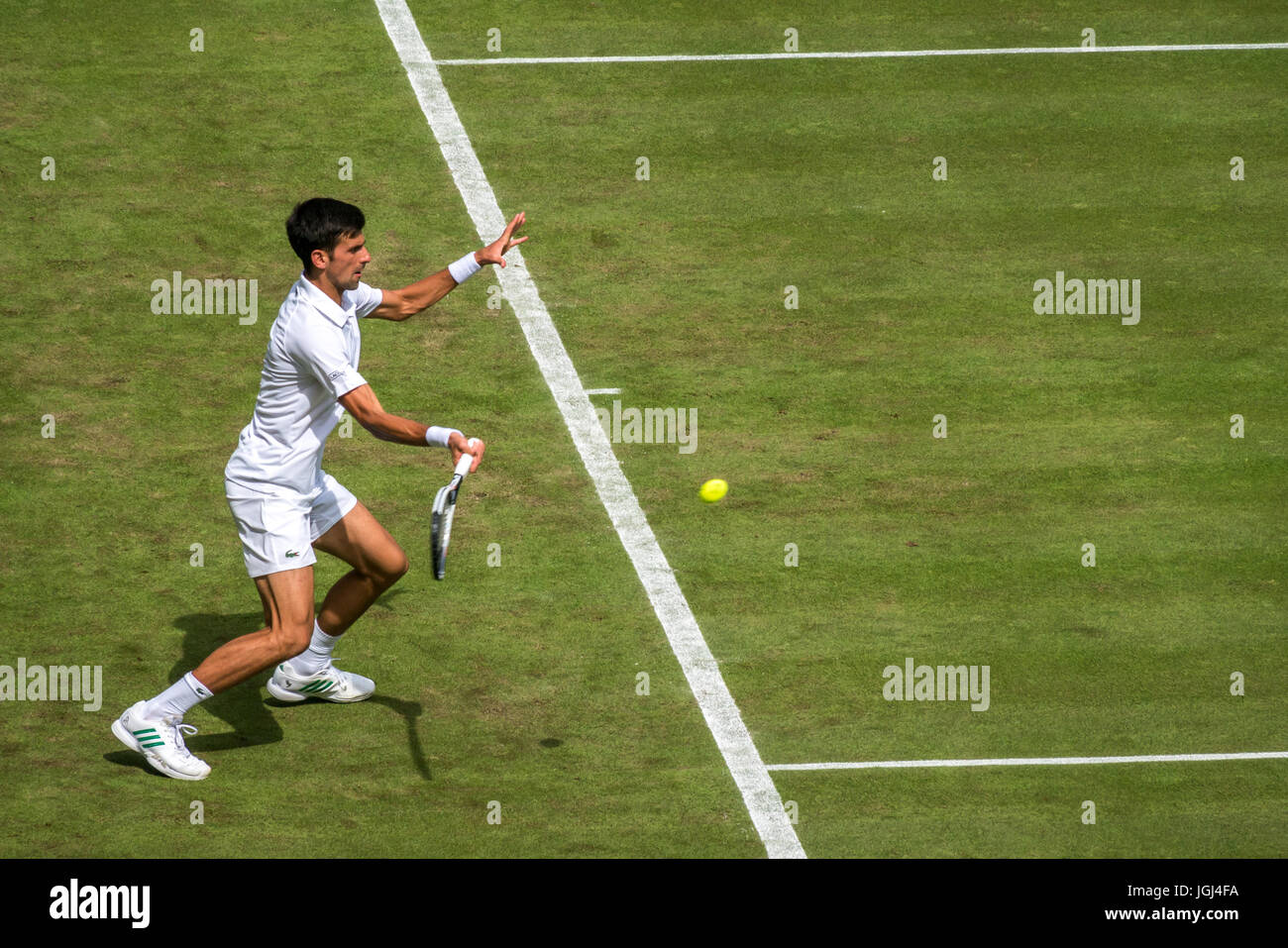 Novak Djokovic returns ball on Centre Court Wimbledon tennis championship 2017, London, England, UK - Stock Image