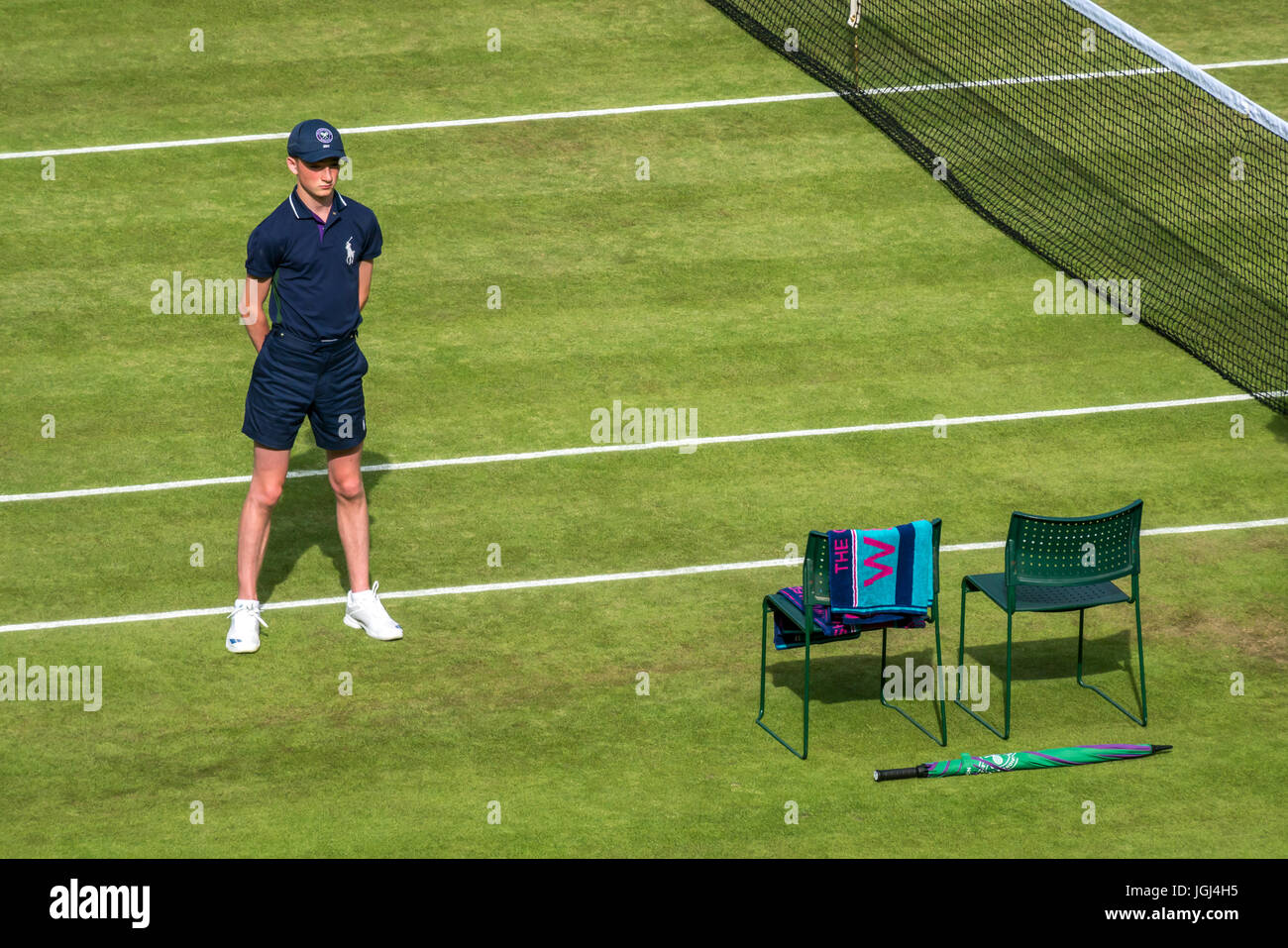 Ball boy standing to attention waiting for start of match and player to come onto Centre Court, Wimbledon tennis - Stock Image
