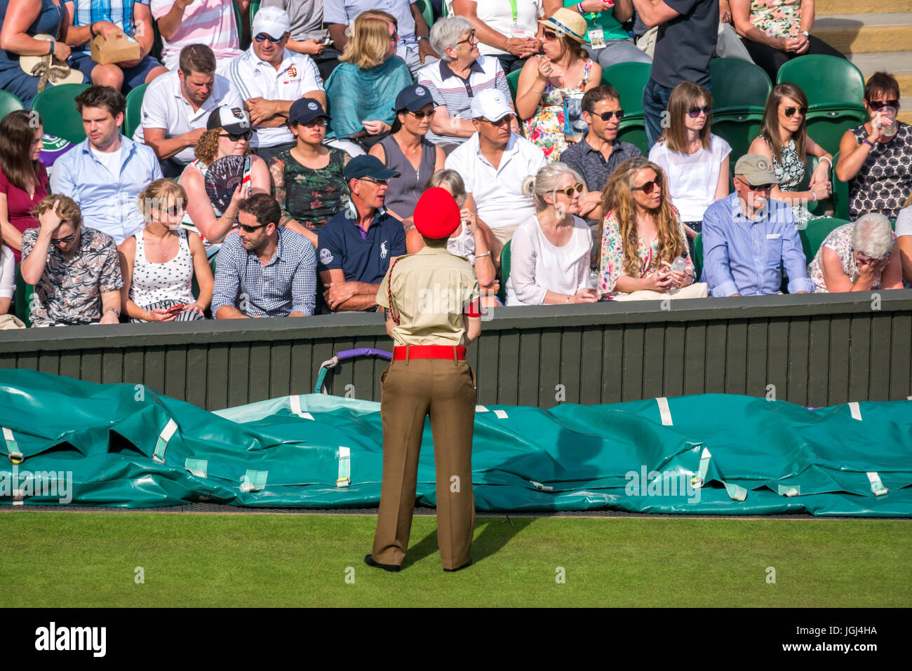 Spectators on Centre Court Wimbledon tennis championship 2017, London, England UK with armed forces standing to - Stock Image