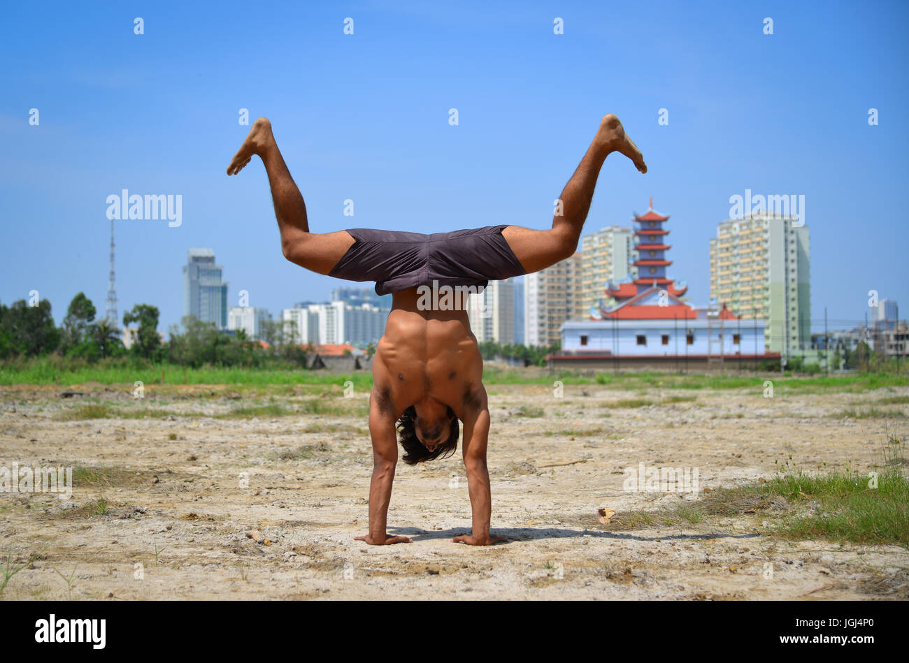 An Indian Man Doing Advanced Yoga Poses At Sunny Day With Cityscape Background