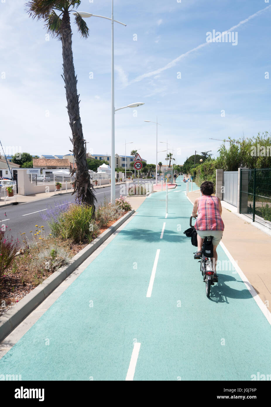 Woman cycling along a cycle path toward Valras plage, Hérault department, France - Stock Image