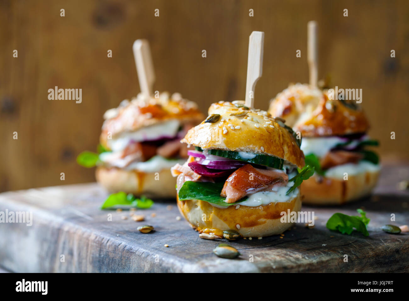 Seeded brioche buns with hot smoked salmon, beetroot and rocket salad - Stock Image