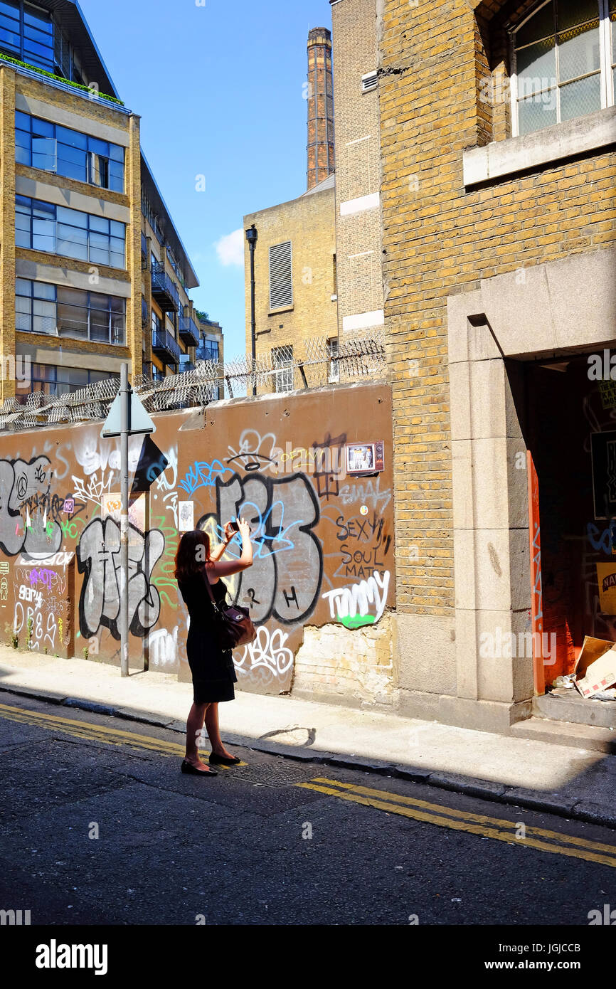 Person taking photographs of the graffiti in Corbet Place near Brick Lane, Shoreditch, London E1 using her smartphone Stock Photo