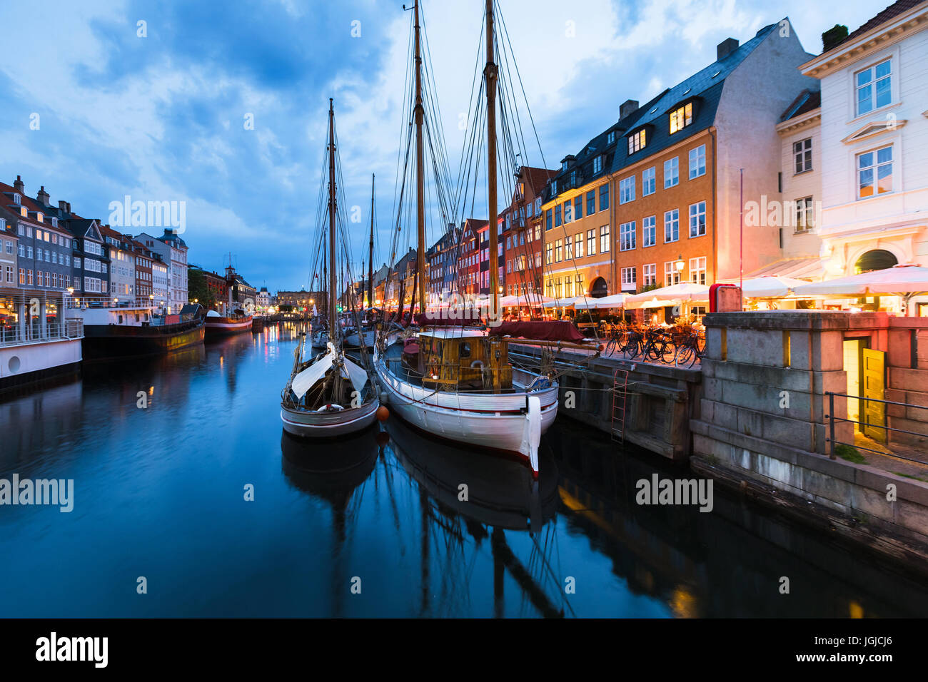 Copenhagen Nyhavn (New Harbor) district with city lights after sunset during blue hour with wooden sailing ship - Stock Image