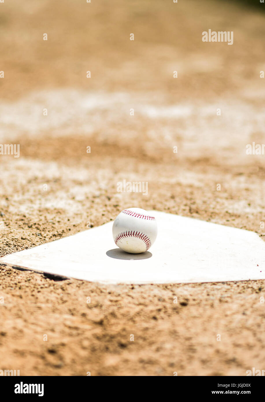 Baseball on home plate on a ball field Stock Photo