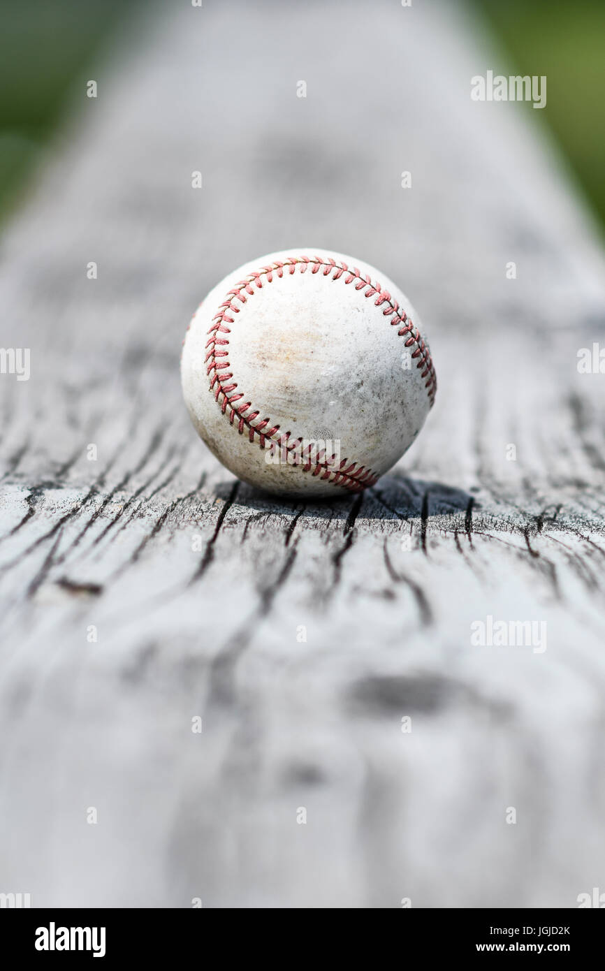 A worn white baseball on a weathered bleacher bench - Stock Image