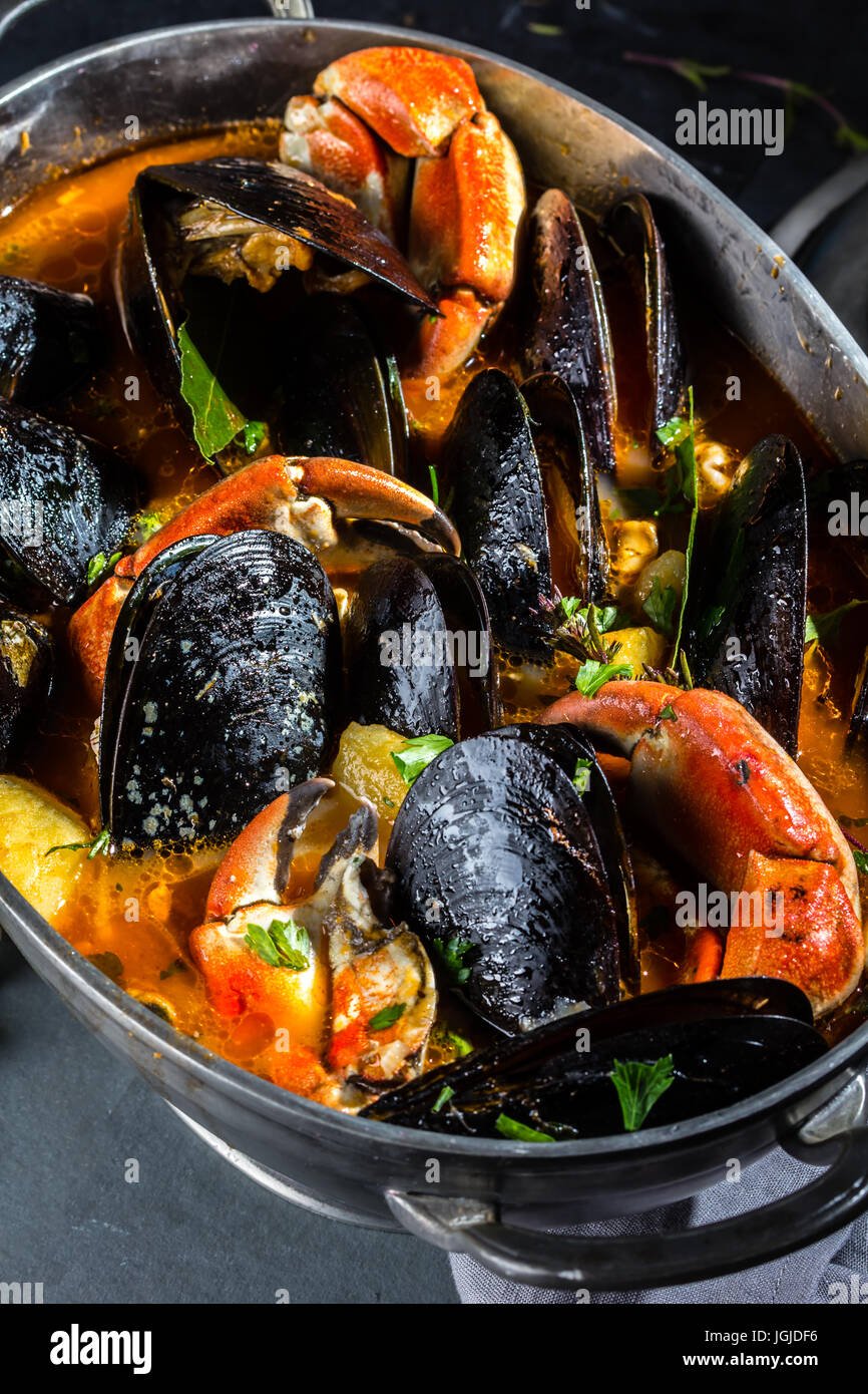 Seafood mussels crabs soup in metal pot - Stock Image