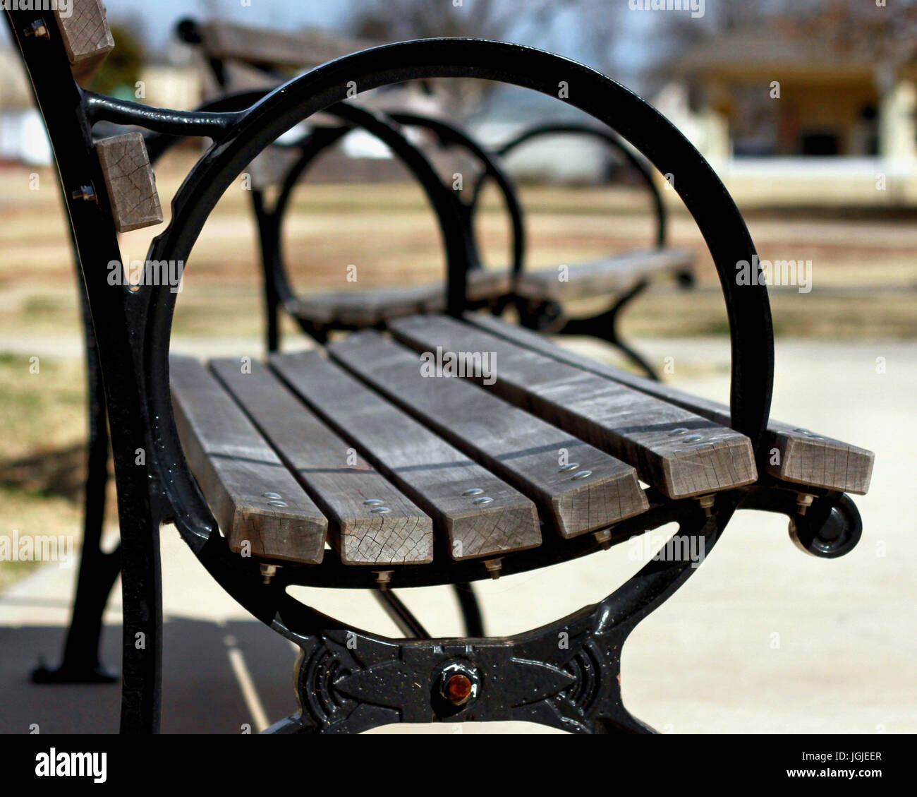 A view through the round armrests of park benches in Oklahoma City. - Stock Image