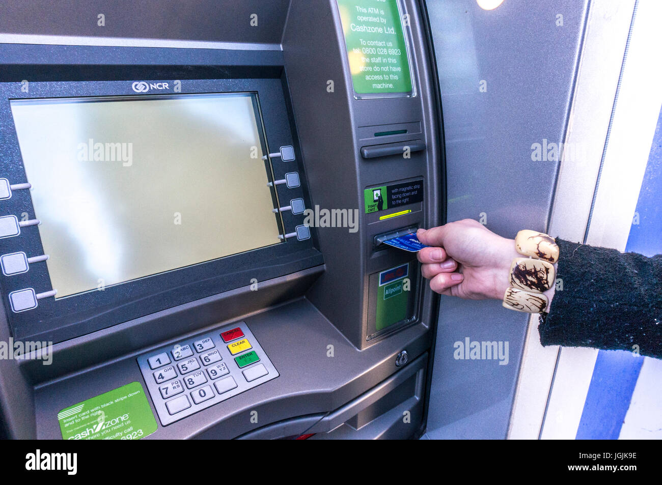 A woman's hand, bearing a large bracelet, inserting a credit or debit card into a cashpoint ATM machine, to - Stock Image