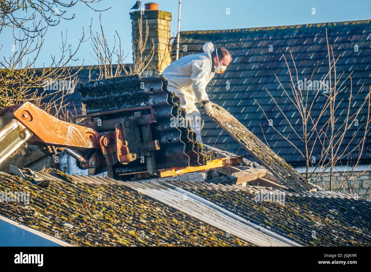 A man wearing protective clothing while removing asbestos roofing from an old barn. Lincolnshire, England, UK. - Stock Image