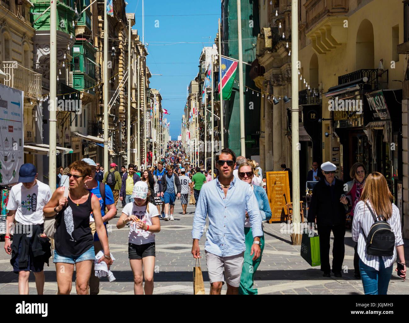 Pedestrians walk over Republic Street / Triq Ir-Repubblika at Valletta  / Malta. - Stock Image