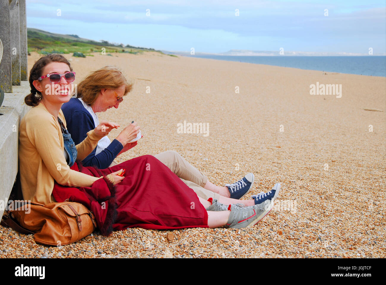 Chesil Beach, Dorset, UK. 7th July, 2017. Two women enjoy a picnic on Chesil Beach, West Bexington, as the onshore - Stock Image