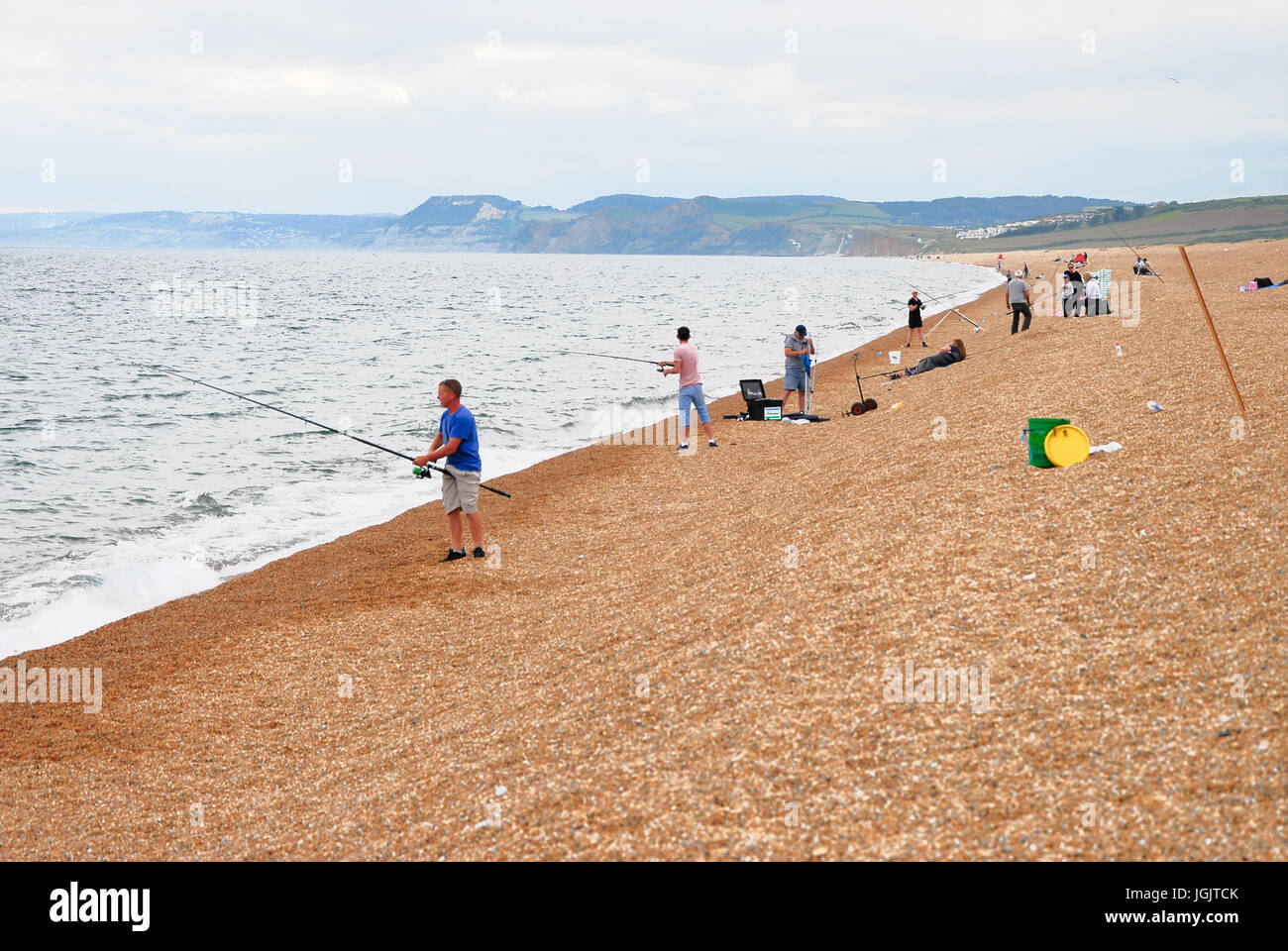Chesil Beach, Dorset, UK. 7th July, 2017. People enjoy fishing on a balmy Chesil Beach, West Bexington, as the onshore - Stock Image