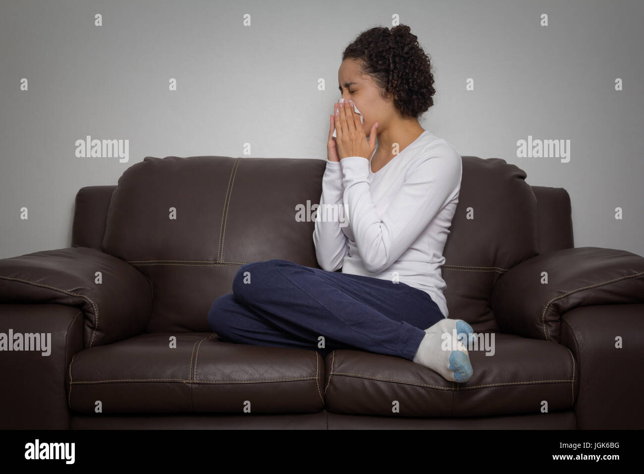 Young woman is sick. She is at home wearing pajamas and sitting on the sofa at home. Stock Photo