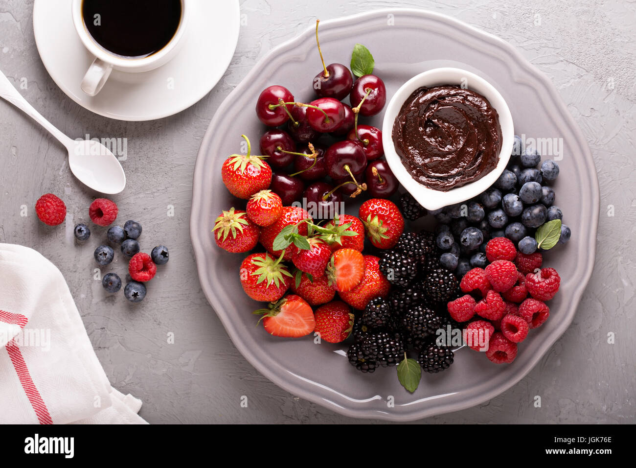 Fresh berries with chocolate sauce for breakfast - Stock Image