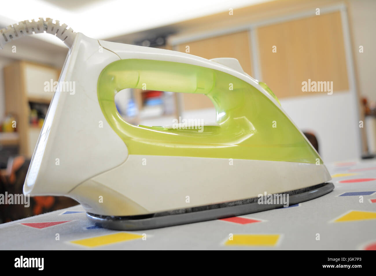 a sad iron isolated on a ironing table - Stock Image