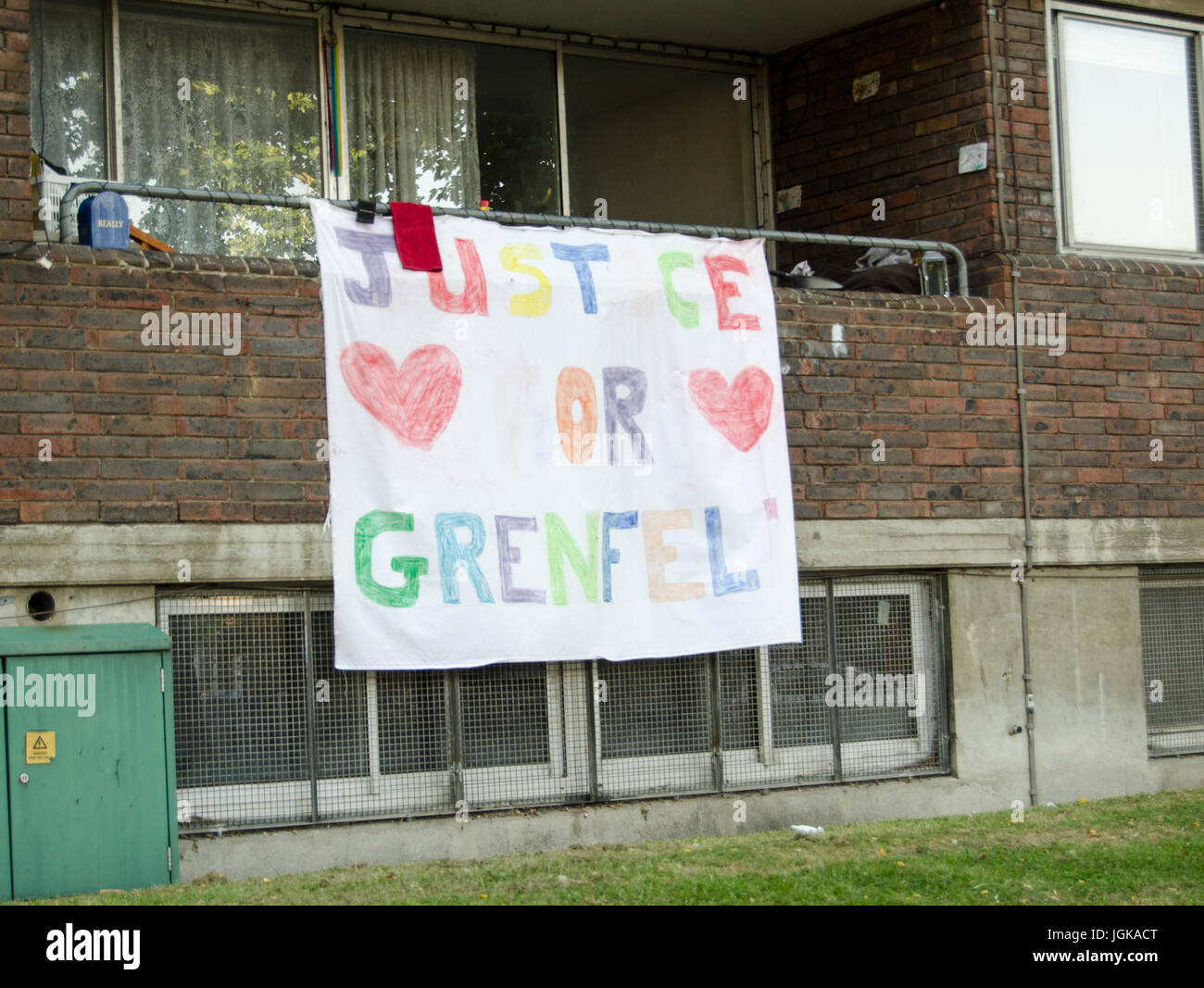 Hand drawn banner calling for Justice for Grenfell displayed on the balcony of a flat next to the Grenfell Tower - Stock Image
