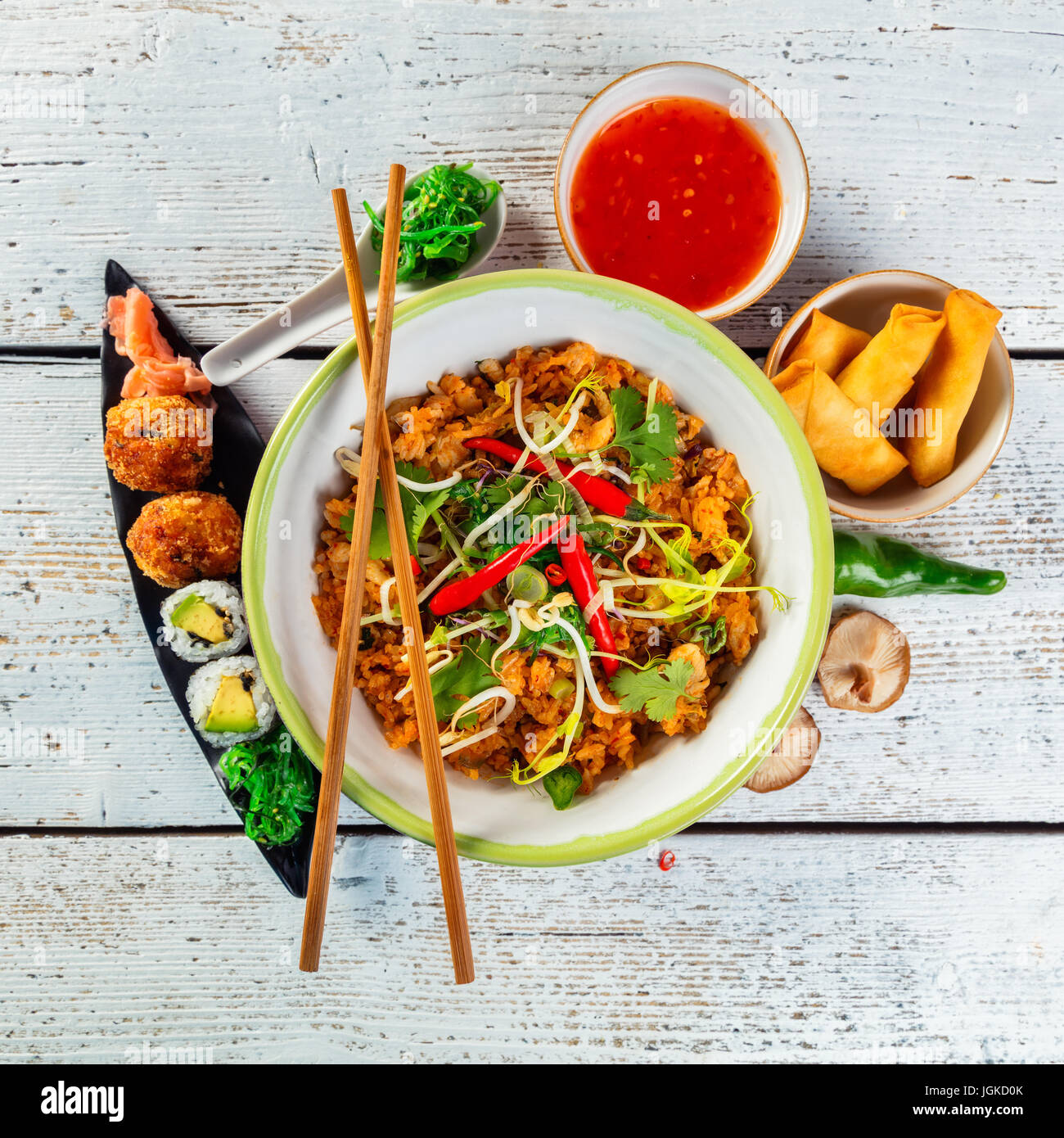 Asian chicken and prawns curry with rice and sushi pieces, top view, served on old wooden planks. - Stock Image